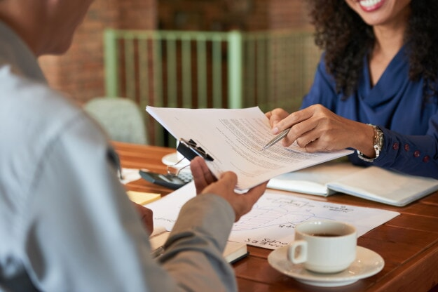Smiling woman handing a document to a man facing her while pointing a pen at the document.